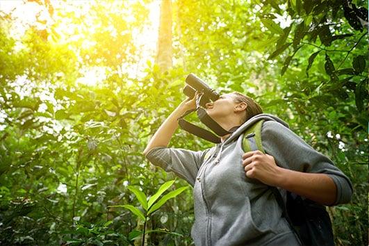 Female birder looking through binoculars