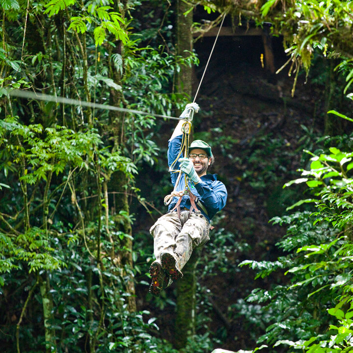 Smiling man riding zipline