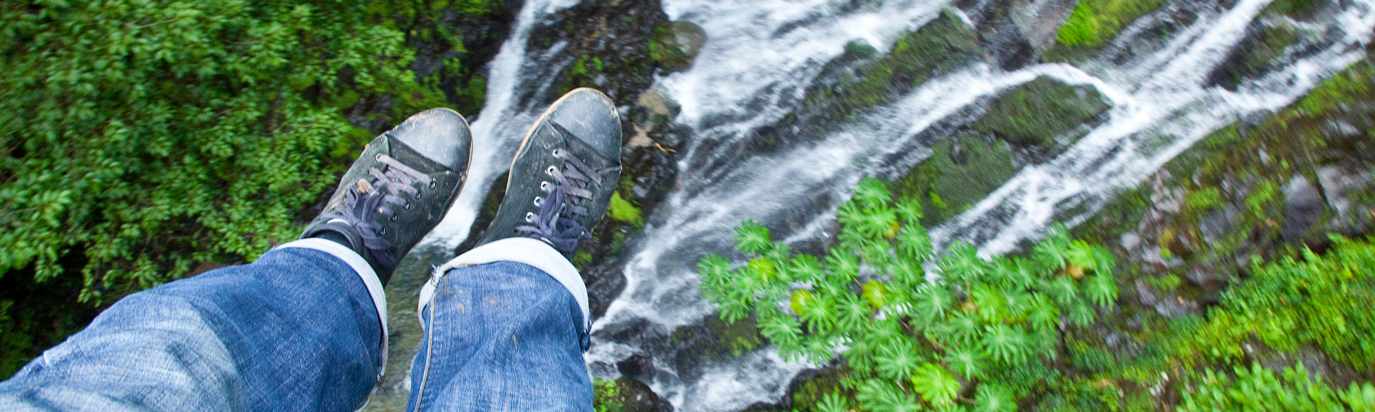 Close up of person's feet riding biplane over waterfall